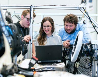3 people around laptop - automotive demand planning - DemandCaster