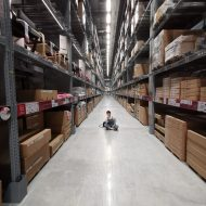 person sitting on shop floor in aisle in warehouse | inventory optimization | DemandCaster