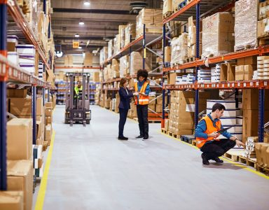 workers in warehouse full of boxes | DemandCaster